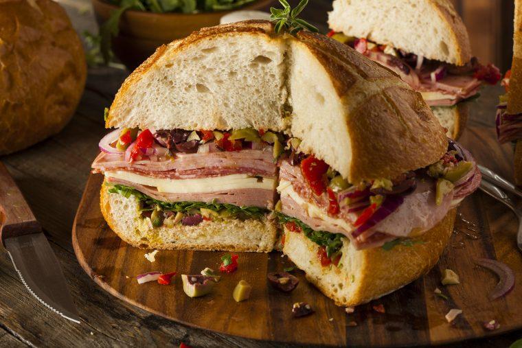 new-orleans style muffuletta sandwich with kentucky legend ham, salami, turkey and olive spread